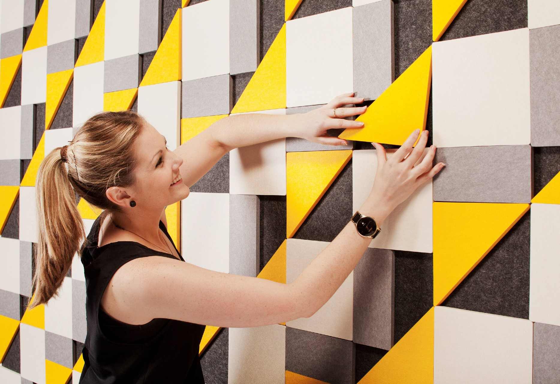 woman-installing-acoustic-geometry tiles